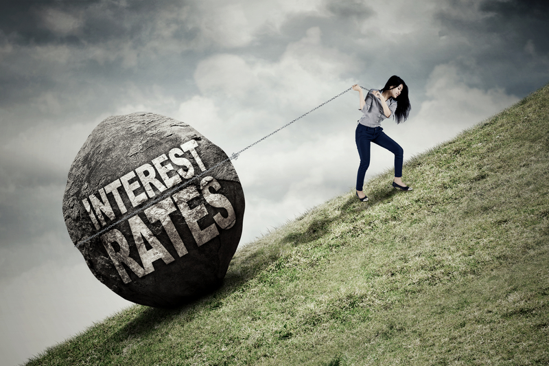Businesswoman pulling big stone with text of interest rates while climbing a hill